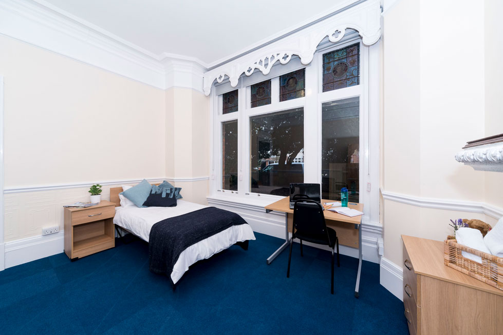 Large single room in a Waldegrave Park house, showing bed, bedside table, desk and drawers